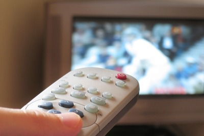 Close-up of TV remote control with sport on TV in the background